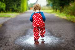Close-up of little toddler girl wearing rain boots and trousers and walking during sleet, rain on cold day. Baby child. In colorful fashion casual clothes royalty free stock photos