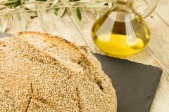 Close-up of a loaf of homemade bread with sesame seeds, ampoule of extra virgin olive oil and an olive branch in selective focus stock photo