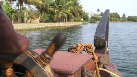 Close up of local steering boat through riverbank