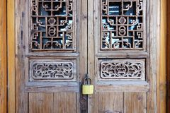 Locked door. The close-up of locked Chinese classcal wooden door with carved designs Stock Images