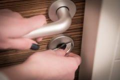 Close up of locking or unlocking door. Female hands locking or unlocking the door Royalty Free Stock Photo