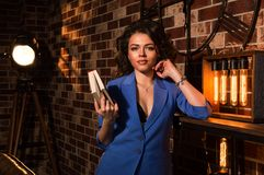 Close up. Loft. Portrait of a sexy girl in a blue jacket witk a book in her hands. Spotlight and brown brick wall in the