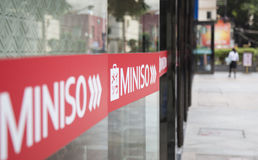 Close up of the logo of Miniso in front of a store Stock Photography