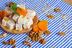 Close-up of lokum with vivid dried apricots, leaves of mint, walnuts and crumbs of nuts on a striped background. stock image