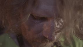 Close-up of the long-haired blacksmith in the forge. Very serious look. Serious men`s work.