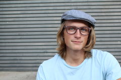 Close up of long haired blond male wearing glasses and news paper boy hat with copy space on the left Stock Photo
