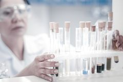 Close up look on female researcher taking test tube with liquid. Only this one is needed. Scaled up view on a set of test tubes with different liquids and hands stock photos