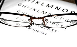 Close-up look of glasses with a letters in the back Stock Image