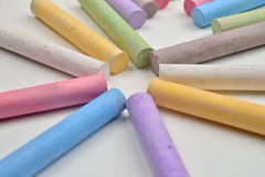 Close up of a lot of colored chalk pieces on on a white backgrou Royalty Free Stock Photo