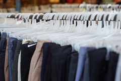 Close up a lot of rack of cloths hanging in a row on shelf, selective focus Stock Images