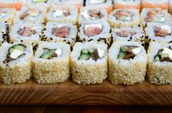 Close-up of a lot of sushi rolls with different fillings lie on a wooden surface. Macro shot of cooked classic Japanese food with. A copy space stock photos