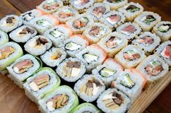 Close-up of a lot of sushi rolls with different fillings. Macro shot of cooked classic Japanese food. Background image.  royalty free stock photos