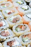 Close-up of a lot of sushi rolls with different fillings. Macro shot of cooked classic Japanese food. Background image.  royalty free stock photography