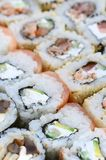Close-up of a lot of sushi rolls with different fillings. Macro shot of cooked classic Japanese food. Background image.  stock image