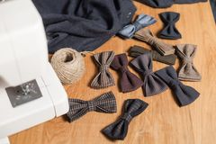 Close-up lots of ready made butterfly bow ties made of wool in the foreground, adds a finished product. Good looking young man working as a tailor and using a Royalty Free Stock Photos