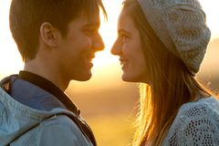 Close up of in love couple at sunset. Close up portrait of young couple with in love face expression at sunset Royalty Free Stock Photography