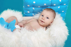 Close-up of lovely baby boy resting on fur bed over blue backgr Royalty Free Stock Photos