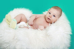 Close-up of lovely baby boy resting on fur over green Stock Image