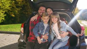 Close up of lovely cheerful trendy family which sitting in the trunk and posing on camera with sincerely smiles