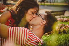 Close up of lovely couple lying on green grass in park, kissing and spending time together.  Stock Images