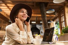 Close up of a lovely girl in hat sitting at the cafe table indoors stock photo