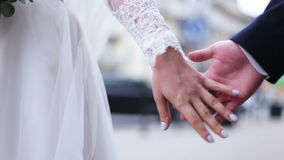 Close up of lovers wedding couple holding hands at the street. slow motion