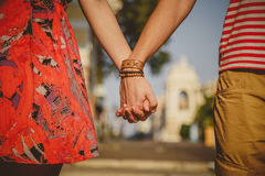 Close up of loving couple tightly holding hands while walking the city street. Dating and love concept Stock Photos