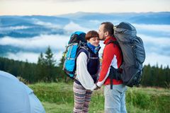 Close-up of loving pair of tourists enjoying each other and morning in mountains. Close-up of a loving pair of tourists enjoying each other and the morning in royalty free stock photography