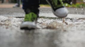 Close-up, Low angle, Unrecognizable Kids Running Through Puddles Summer Day After Rain. Carefree Children Run in Puddles stock footage