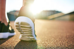 Close up low angle view of running shoes. With while soles on an empty road as the sun highlights the distance Stock Images