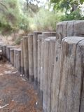 A low fence made of wooden trunks in the park. Close up of low fence made of wooden trunks in the park, natural colors royalty free stock image