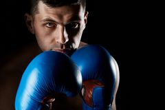 Close up low key portrait of an aggressive muscular fighter, showing his fist isolated on dark background. Close up low key portrait of a aggressive muscular Royalty Free Stock Photos