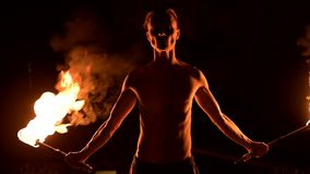 Close-up. Low key. Young male with long hair and bare torso rotates burning torch outdoors on a black night video slow. Motion. Modern fakir does tricks with a stock video