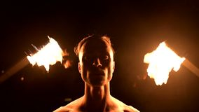 Close-up. Low key. Young male with long hair and bare torso rotates burning torch outdoors on a black night video slow. Motion. Modern fakir does tricks with a stock footage
