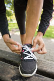 Close up low section of sporty woman wearing shoes in park Royalty Free Stock Image