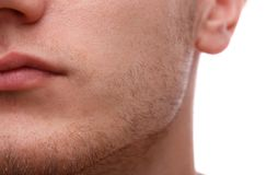 Close-up of the lower part of a man`s face. Isolated over white background. Close-up of the lower part of a man`s face, chin, bristles. Isolated over white