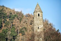 Round Tower with crows in Glendalough. Close up lower view of the round tower in Glendalough monastic site on Ireland`s east coast Stock Photo