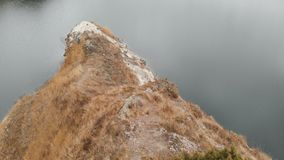 Close-up Lucht hoogste mening van een meisjesfotograaf in een gele hoed met een rugzak die langs een bergweg naar a gaat stock video