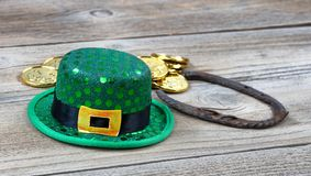 Close up of Lucky hat for St Patrick on rustic wooden background. Lucky green hat, horseshoe and gold coins for St Patrick on rustic wooden boards in close up Stock Images