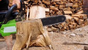 lumberjack or logger hands cutting wood for logs using his chainsaw. Woodcutter working and sawdust fly to sides. stock video footage