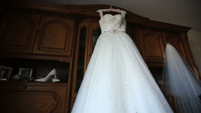 Close-up of luxurious white wedding dress hanging up by the window on the wooden shelf background stock video footage
