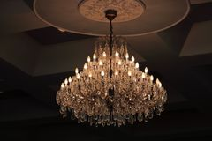 Close up luxury crystal chandelier hanging under ceiling in the room. Close up luxury crystal chandelier hanging under ceiling in the room Stock Photos