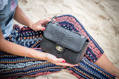 Close up of luxury handmade snakeskin python handbag in woman hands. Tropical Bali island. stock image