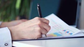 Close-up, mãos fêmeas no desktop, ao lado de um portátil, guardando uma pena preta, um documento, gráficos de negócio Negócios filme