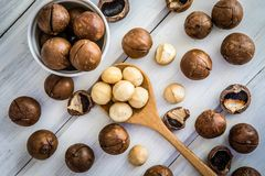 Close up Macadamia nuts on  white wooden background , a superfoo Royalty Free Stock Images