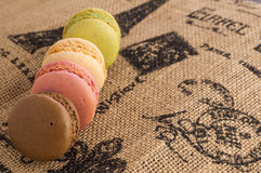 Close up macaroons on the jute tablecloth. With french motive print and space for text royalty free stock images