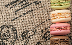 Close up macaroons on the jute tablecloth. With french motive print and space for text stock photos