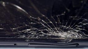 Close-up macro of broken dark glass. Elements of smartphone, screen, hammer blow, dropped smartphone. Close-up macro of broken dark glass. Abstract black stock photo