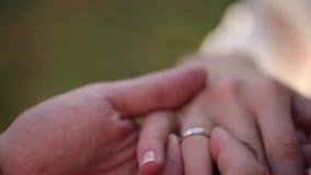 Close up macro das alianças de casamento que põe o anel sobre sua joia do diamon do ouro branco do dedo video estoque