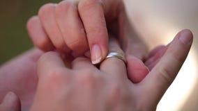 Close up macro das alianças de casamento que põe o anel sobre sua joia do diamon do ouro branco do dedo vídeos de arquivo
